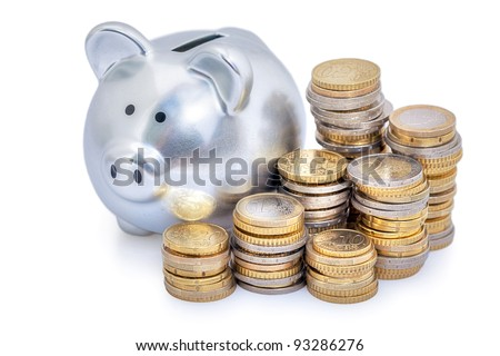 Stacks of Euro coins next to a silver piggy bank.  White background