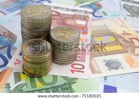 Stacks of Euro coins on Euro banknotes