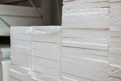 Stacks of expanded polystyrene in packaging at a building materials warehouse in a store. The insulation lies on metal racks in the distribution warehouse.