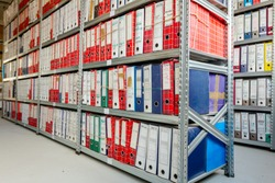 Stacks of files and paperwork placed in bookshelves with folders and documents in binders archive, storage room.