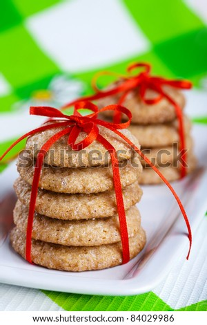Stacks of gingerbread cookies tied with red ribbon on white plate