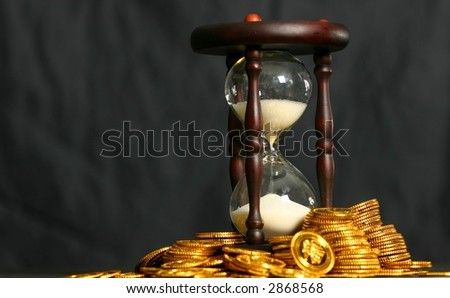 Stacks of gold coins with hourglass