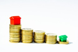 stacks of gold coins with red and green houses, business and financial motives, housing topics, investments, coins, money, banking topics with coins and red houses