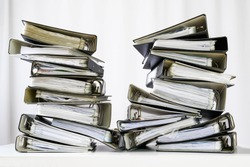 stacks of many ring binder with files, folders and documents on an office desk, concept for too much work and burn out in the business, selected focus