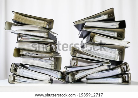 stacks of many ring binder with files, folders and documents on an office desk, concept for too much work and burn out in the business, selected focus #1535912717