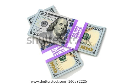 Stacks of new hundred dollar bills isolated on white background.  This newly redesigned US currency was released for circulation in October of 2013.