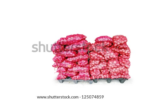 Stacks of onion in red plastic sacks on a plastic cargo pallet, isolated against white.