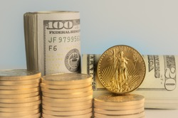 Stacks of pure gold eagle coins in front of rolled bankrolls of USA dollar bills