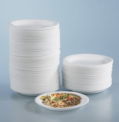 Stacks of round polystyrene plates and fried mee on a round plastic plate.