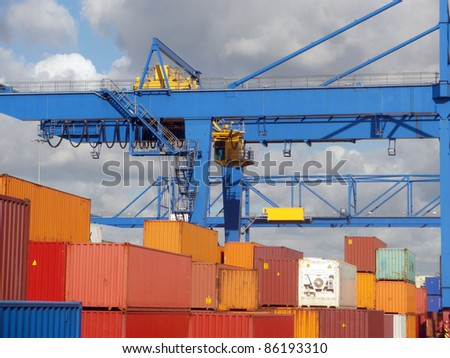 Stacks of shipping containers and fragment  of two crane