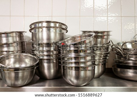 Stacks of stainless steel mixing bowls on a stainless steel shelf in an industrial kitchen