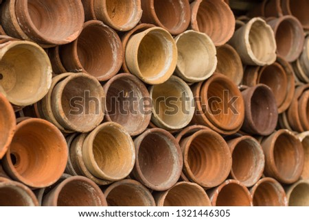 Stacks of terracotta flowerpots in a gardeners potting shed at botanical garden. Many stacked ceramic pots for plants. Old ceramic pots. #1321446305