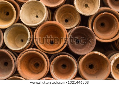 Stacks of terracotta flowerpots in a gardeners potting shed at botanical garden. Many stacked ceramic pots for plants. Old ceramic pots. #1321446308