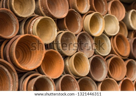 Stacks of terracotta flowerpots in a gardeners potting shed at botanical garden. Many stacked ceramic pots for plants. Old ceramic pots. #1321446311