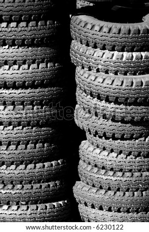 Stacks of used tires piled outside - can also represent environmental issues, industrial waste, recycling, texture, etc. - stock photo