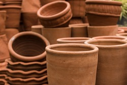 Stacks of various terracotta pots for plants for sale at a garden store.
