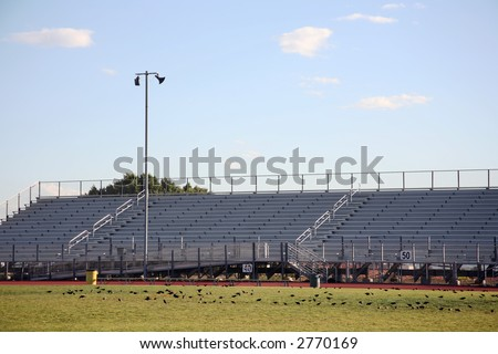 Stadium bleachers facing a sports field with beautiful sky above