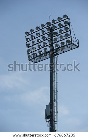 Stadium floodlight with metal pole with blue sky in the football stadium. #696867235