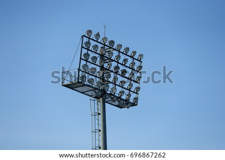 Stadium floodlight with metal pole with blue sky in the football stadium. #696867262