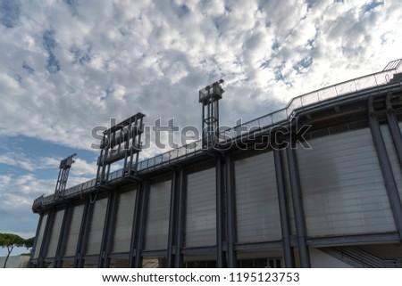 Stadium floodlights against cloudy sky #1195123753