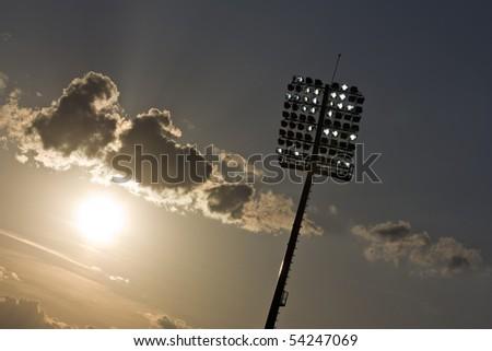 Stadium lights and sunset - stock photo