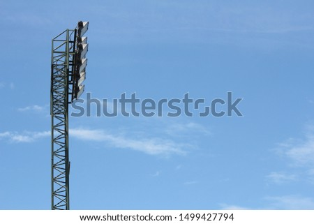 Stadium lights tower, spotlights illuminate, against with blue sky background