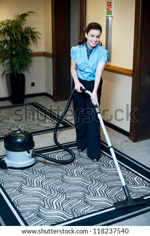 Staff cleaning carpet with a vacuum cleaner. Smiling and enjoying her work