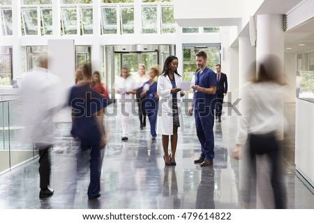 Staff In Busy Lobby Area Of Modern Hospital
