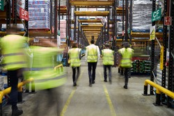 Staff in reflective vests walking in a warehouse, back view