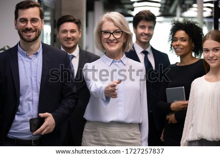 Staff members team gather in office hallway look at camera leader boss stretched hand greeting client ready start negotiations. HR manager invite you passing job interview, staffing in company concept