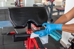 Staff using wet wipe and disinfectant from the bottle spraying sit up bench in gym. Antiseptic,disinfection ,cleanliness and healthcare. Anti bacterial and Corona virus COVID19.