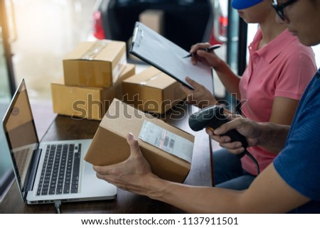 staff work together delivery the box logistic and use barcode scanner and computer