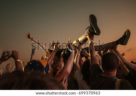 Stage diving. Crowd surfing during a musical performance #699370963