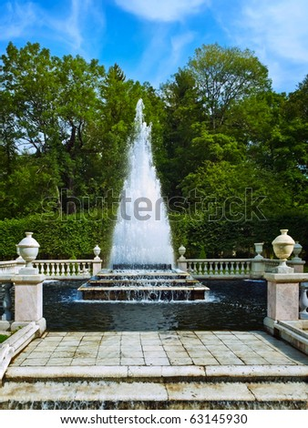 stage fountain in the park over green trees and blue sky, Peterhof, St. Petersburg