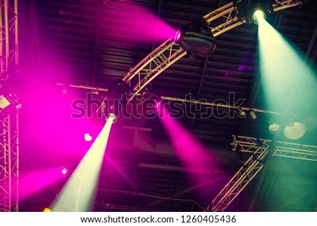 Stage lights on concert. Lighting equipment with multi-colored beams. Bottom view. Selective focus. Copy space #1260405436
