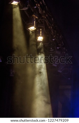 Stage lights. Several projectors in the dark. Multicolor light rays from the scene of spotlights on stage in smoke during an entertainment show. Laser show on the nightclub scene