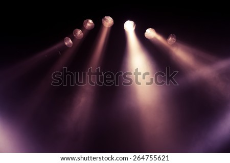 Stage lights. Several projectors in the dark. Purple spotlight strike through the darkness #264755621