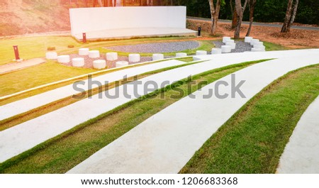 Stage outdoors / stage show with Park bench Cement and pathway in the garden - amphitheater open air in the garden park