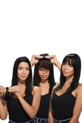 Staged photo of brunette lady which is trying on black bangs. Natural looking bangs are fixing on the clip. Girl in black top and blue jeans is showing three phases of hair extension.