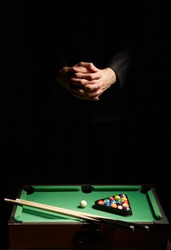 Staged photo of male hands with interlocked fingers over table billiards in the twilight. The pool set includes two billiard-cues, a board with green cloth and game balls of different colours.