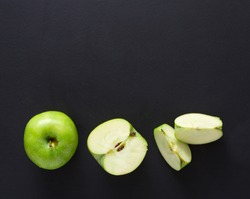 Stages of cutting green apple on black background. Chopping fresh fruit, cooking healthy food