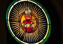 Stained glass window depicting Catholic devotion of Immaculate Heart of Mary pierced by a sword