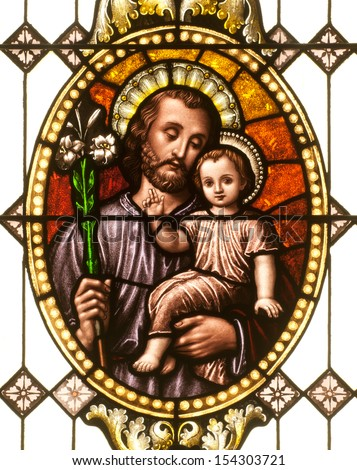 Stained glass window depicting Saint Joseph holding the child Jesus