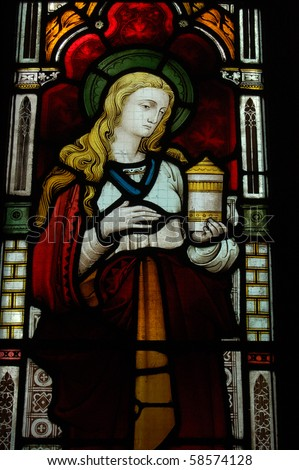 Stained glass window depicting Saint Mary Magdalen with her traditional attribute of a pot of oinment. From an early Victorian window created in the middle of the 19th century