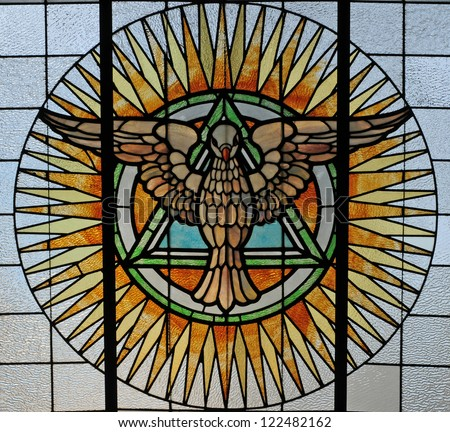 Stained glass window depicting the Holy Spirit as a dove and Trinity as triangle