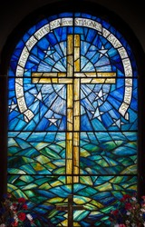 Stained glass window in a church on St Agnes, Isles of Scilly, U.K. Depicting a cross against the sky and sea.