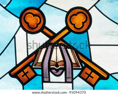 Stained glass window of Bible, priest's stole and keys