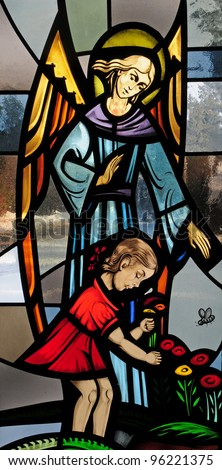 Stained glass window of guardian angel with little girl in red dress picking flowers
