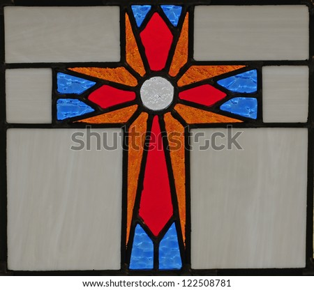 Stained glass window of red, blue and gold cross