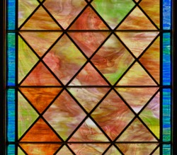 Stained glass window with diamond shapes and overall red brown color
